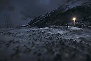A single street light illuminates the snowy ground on a dark winter night in Bergsfjord, Finnmark, Norway