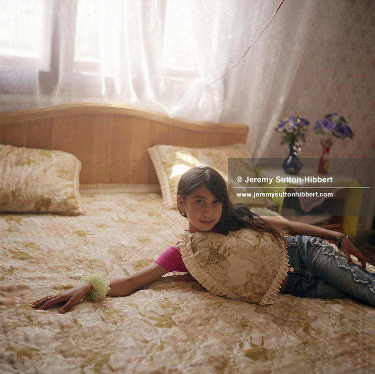 A young Roma girl poses on a bed, in a style imitating images of Western fashion models that she has seen. Roma girls like to imitate Western women and do not wish to be seen as Roma or gypsies...