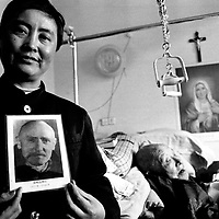 ANGUO, APRIL 1, 2001 : sister Francis (L) shows a photo of Vincent Lebbe, a Belgian missionary who worked in China in the 40ies , while his former student, a 98 year old priest, lies in a bed behind. Lebbe is considered controversial by the Vatican, but in China and Taiwan he's worshipped as a Saint.  China cut relations with the Vatican in the early fifites and since then, established a Patriotic catholic Church that's controlled by Chinese authorities.<br /> Catholics who refused to give up their ties with the Vatican, started worshipping in underground churches and consequently were persecuted for a long time. Since the late nineties though, relations with the Vatican informally started to improve. Although China still has no diplomatic relations, many representatives from official churches met the pope John Paull II secretely . Since pope John Paul II death in spring 2005, thousands of catholics have commemorated John Paull II  in special masses throughout China.