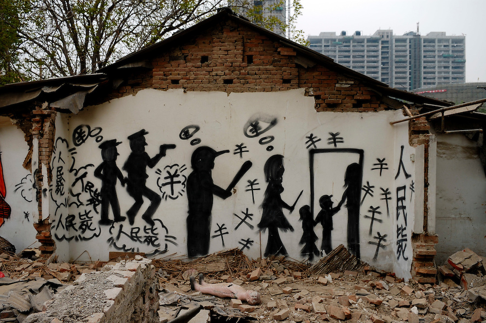 """Protest against the destruction of old Beijing. Graffiti on hutong housing being knocked down for new construction in the build-up to the Olympic Games, showing police, thugs and a family member chasing others from their home, surrounded by the Yuan symbol (the Chinese currency). The other characters read: """"People's Execution"""" a clever and pointed play on words, as it sounds like """"People's Money"""" or Renmin Bi - the official name for the currency. ..From China [sur]real © Mark Henley.."""