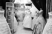 A shopkeeper sits in between wedding dresses in her store in the city center of Tehran. Iran, 2007