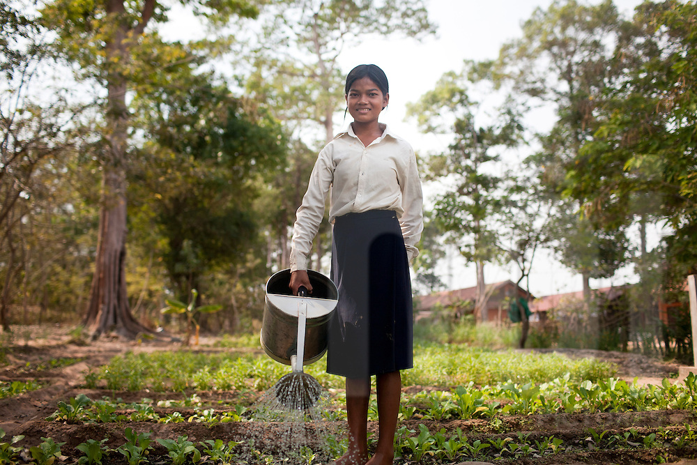 A young Cambodian pupil smiles at the camera as she waters a garden during break-time at school, Angkor, Cambodia, Southeast Asia