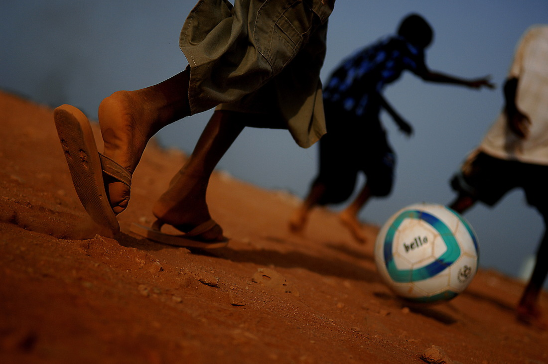 """U.S. Marines from the 8th Provisional Security Detachment, Combined Joint Task Force - Horn of Africa, play soccer with children in Negad, Djibouti, Africa, on May 22, 2008, as members of the U.S. Air Force Central Command Band """"Falcon"""" sets up to play a concert for the village. — © /"""