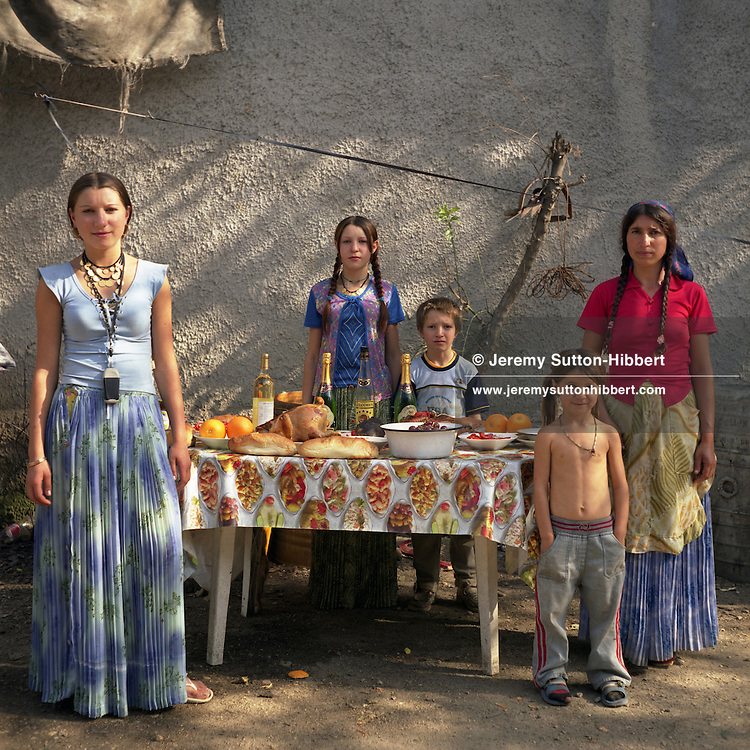 A Roma family stand by a table of food and wine, on the day that they celebrate a Romanian Orthodox religious holiday festivity,  in the Roma community of Sintesti. The girl on left of picture is wearing a mobile telephone around her neck, phones have become a status symbol within the camp..