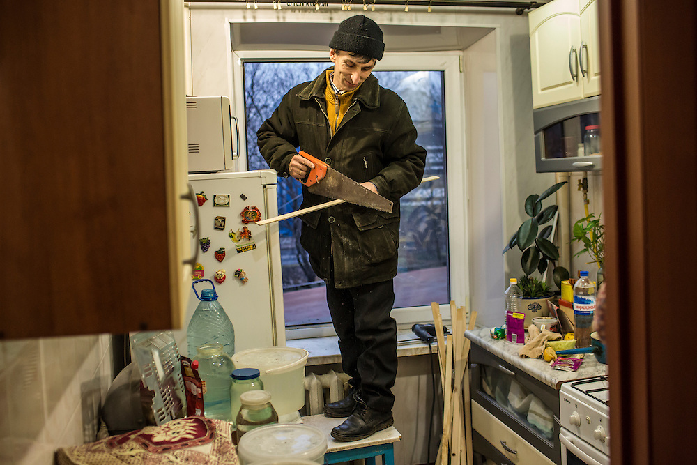 DONETSK, UKRAINE - FEBRUARY 2, 2015: A man makes repairs to a broken window in the kitchen of Yekaterina Malkova, 71, whose apartment was damaged when a shell landed just ouside the building overnight in Donetsk, Ukraine. Malkova is paralyzed on the left side of her body, making it difficult to travel. Her daughter lives in the United States, and her husband passed away on January 27 of this year. Ongoing fighting has killed scores of civilians since a tenuous ceasefire collapsed in late January. CREDIT: Brendan Hoffman for The New York Times