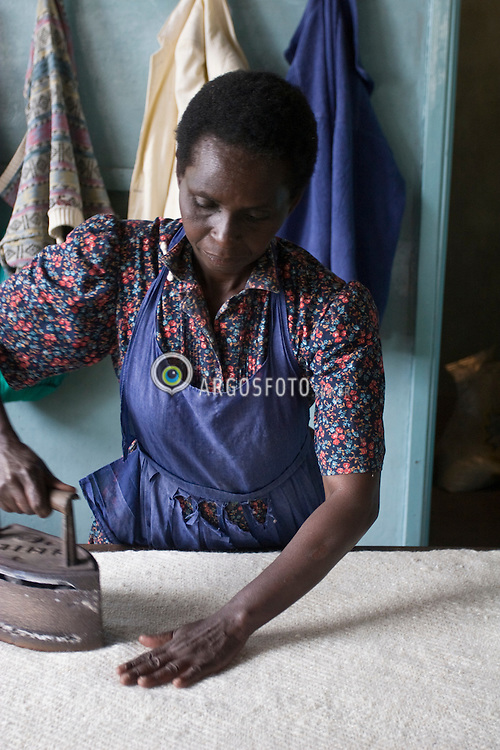 A African woman in Samburu works at a traditional loom. Vertical looms were probably the first to be invented. A loom is a machine or device for weaving thread or yarn into textiles. / Mulher africana, do distrito de Samburu, trabalhando em tecelagem artesanal