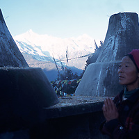 """MEILI MOUNTAIN, DECEMBER 17, 2000: a Tibetan nomad prays at an altar near Mt. Meili in the morning in deqin county, Yunnan province , December 17, 2000..Mt. Meili is the highest peak in Yunnan province and according to supporters from Deqin county, it's a """"proof"""" that the 'real"""" Shangri-La is located in deqin county. The fictuous Mt. Karakal which is described in James Hilton's Lost Horizon, alledgedly is modelled on Mt. Meili in Yunnan province.."""