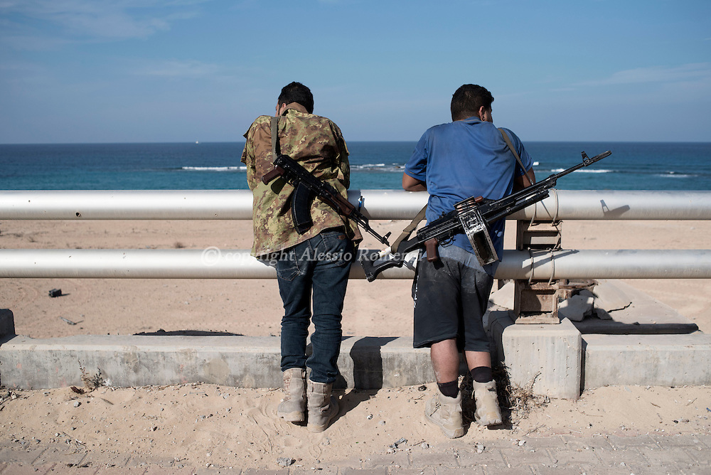 Libya, Sirte: Right after the end of the clashes two fighters of the Libyan forces affiliated to the Tripoli government relax in front of the the sea in Al Jiza neighbourhood on the frontline with ISIS in Sirte on November 24, 2016.  Alessio Romenzi