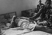 A patient rests on his bed while his friend holds his hand for support after he got injured by  weapon rests at CBL Center of Bujumbura ( Center for injured people). @ Martine Perret . 24 October 2005.