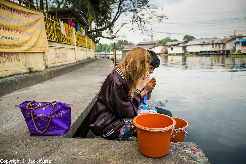 04 JANUARY 2012 - BANGKOK, THAILAND:  A woman prays before releasing fish into Phra Khanong canal to make merit at Wat Mahabut. The temple was built in 1762 and predates the founding of the city of Bangkok. Just a few minutes from downtown Bangkok, the neighborhoods around Wat Mahabut are interlaced with canals and still resemble the Bangkok of 60 years ago. Wat Mahabut is a large temple off Sukhumvit Soi 77. The temple is the site of many shrines to Thai ghosts. Many fortune tellers also work on the temple's grounds.   PHOTO BY JACK KURTZ