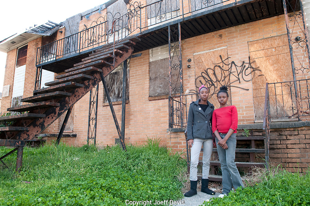 """Nina, 17 and Gigi, 11, pictured in front of the abandoned building next to their home in Vine City. """"It makes me sad and it makes the community look bad,"""" said Nina who wants to be a registered nurse or a surgeon when she grows up. """"I wish they would get some of the dope dealers off the street and get the homeless somewhere to live."""