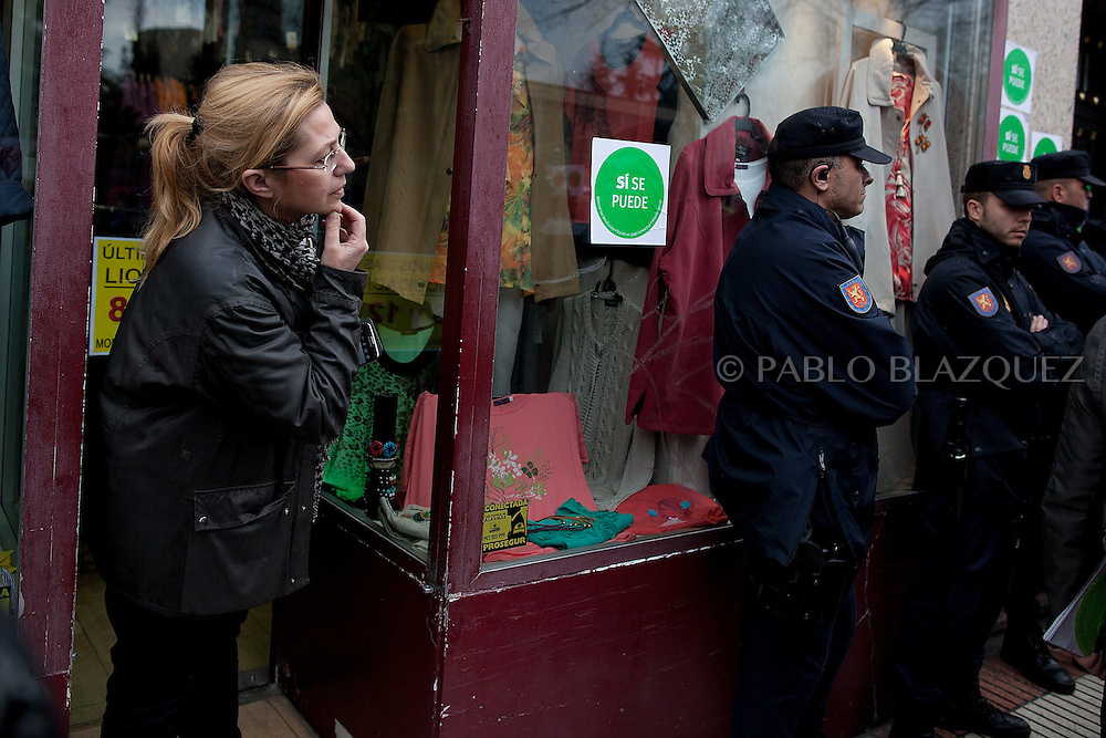 A shop attendance looks at anti-eviction activists and riot police during a 'escrache' outside the house of Popular Party Deputy Mari Luz Prieto, on April 4, 2013 in Madrid, Spain. Placard reads 'Yes we can'. The Mortgage Holders Platform (PAH) and other anti evictions organizations are organizing 'escraches' for several weeks under the slogan 'There are lifes at risk' to claim the vote for a Popular Legislative Initiative (ILP) to stop evictions, regulate dation in payment and social rent outside Popular Party deputies' houses and offices..'Escraches' are form of peaceful public protest that was used in Argentine in 1995 to point to pardoned genocides of Argentenia's Dictatorship within their neighborhoods.
