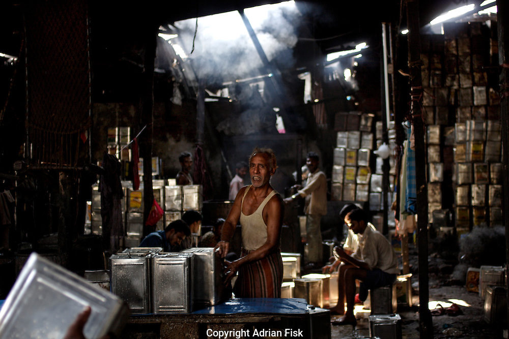 A man looks up as he and others clean vegetable oil tins on 21st Oct 2006. Dharavi is the centre of Bombay's recycling industry.