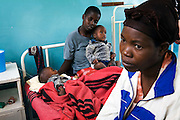 """A mother  watches over her twin sons who are being re-hydrated with intravenous fluids on a paediatric ward at a Cholera Treatment Centre in Harare...Children and adults are treated at Beatrice Road Infectious Diseases Clinic in Harare, Zimbabwe...The clinic is staffed by locals but assisted by MSF. As of 30 May 2009, there were 98 424 suspected cases, including 4 276 deaths reported by the Ministry of Health and Child Welfare (MoHCW) of Zimbabwe since August 2008. Fifty-five out of 62 districts in all 10 provinces were affected. in December 2008, Robert Mugabe declared that """"there is no cholera"""" in Zimbabwe. Failing sanitation and lack of water supply were to blame, workers responsible claimed they had not been paid by the government for several months."""