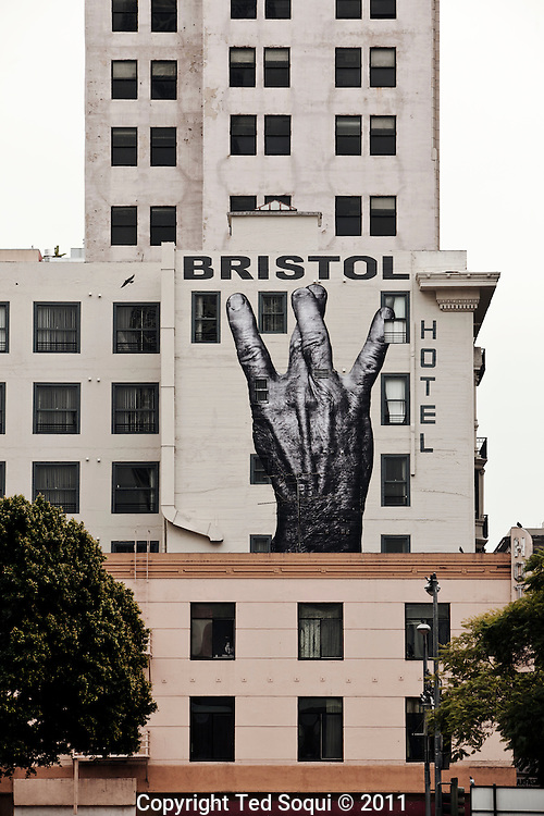 """Street art in Los Angeles..L.A. has become the new ground zero for avant-guard and cutting edge street and graffiti. Artist from around the world now come to L.A. to post their work..A street art piece by French street artist and TED prize winner, JR, on the side of the Bristol Hotel located in downtown L.A. This mural is part of JR's """"The Wrinkles of the City"""" project."""