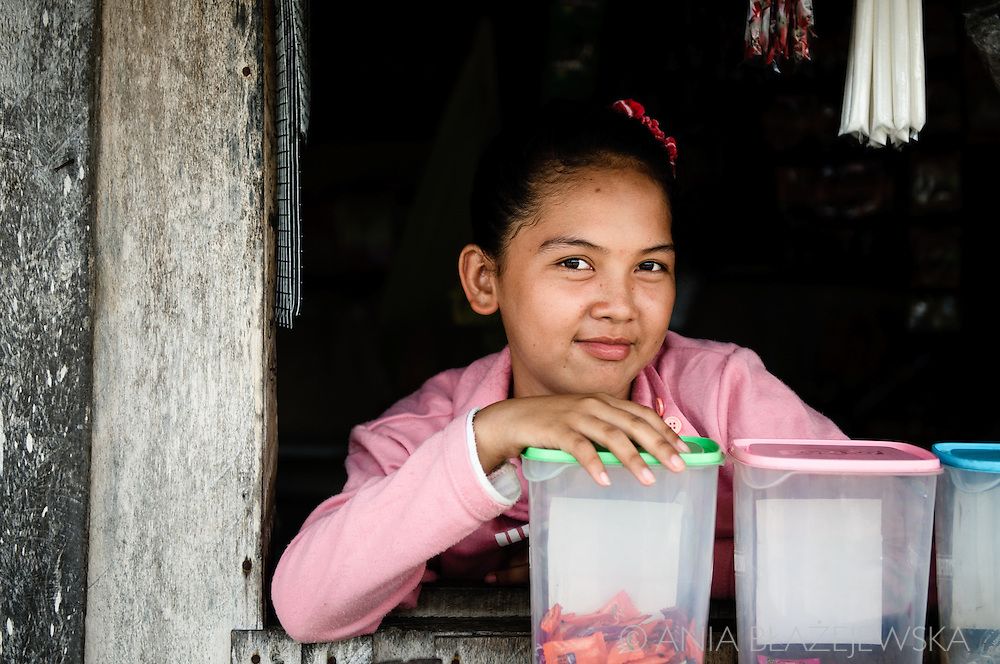 Philippines, Tawi Tawi. Little salesman from Simunul Island posing in her shop.
