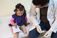 Little Dua'a lost a leg during a rocket attack in her hometown Daraa, Syria. She is being comforted by Dr. Mahmoud, a Syrian refugee <br />