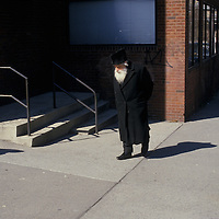 An old man walks along the sidewalk in the Lower East Side of New York City.