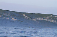 Surfers sit below a giant wave at the 2010 Mavericks Surf Contest held in Half Moon Bay, California on February 13, 2010