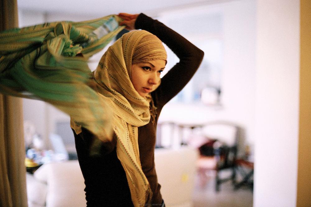 Jeune femme musulmane essayant diff&eacute;rentes combinaisons de hijab chez elle, France 2006. <br /> Muslim woman trying multiple combination of hijab at home, France 2006.