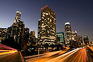 First light from sunrise illuminates downtown Los Angeles wih traffic streaking across the freeway landscape