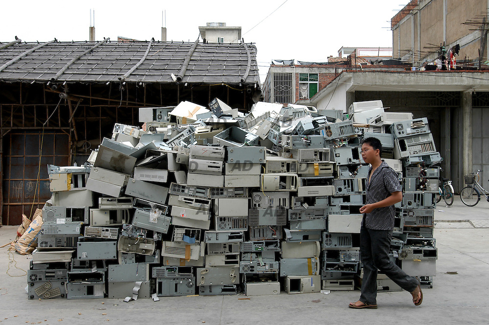 """In Chaoyang county in southern Guangdong province - China's richest - whole farming families have turned into scavengers over the last decade for extra cash..For years, so called """"e-waste"""" from richer countries has found its way to China, where armies of rural poor rummage through computer monitors, central processing units, printers, toner cartridges and other high-tech trash to sell what they can to recyclers. .Plastics, metals and other recyclable materials lay in heaps everywhere, waiting to be trucked to smelters..Electronic waste can contain 1,000 different substances including lead, cadmium, chromium and mercury - heavy metals which are highly toxic..Unwanted electronic junk is seen in open rice fields everywhere, on riverbanks and in ponds, and some families in the area have stopped drinking well water because it has taken on a yellow hue..In April 2000, China specifically outlawed e-waste importation. But occasional crackdowns have done little to curtail recycling, which thrives on corruption and strong market demand.. *** Local Caption *** A pile of computerbox waiting to be dismounted."""
