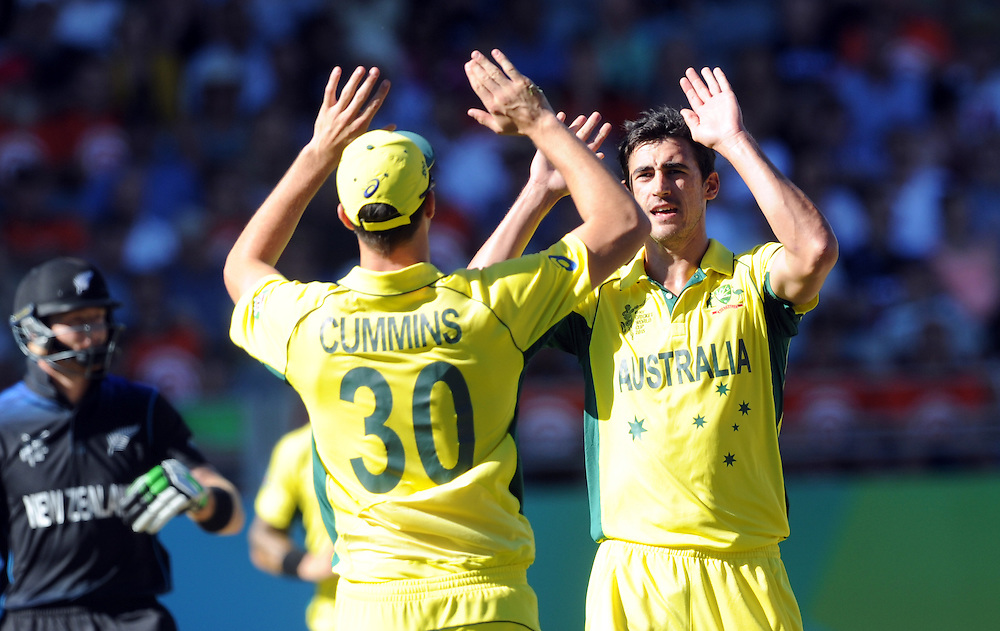 Australia's Mitchell Starc, right, celebrates with Pat Cummins after dismissing New Zealand's Martin Guptil for 11 in the ICC Cricket World Cup at Eden Park, Auckland, New Zealand, Saturday, February 28, 2015. Credit:SNPA / Ross Setford