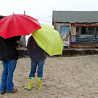Two people under umbrellas stop to inspect cottages that were damaged by Hurricane Sandy storm surge at Roy Carpenter Beach in South Kingstown, Rhode Island on October 30, 2012.   The area was one of the hardest hit by the storm surge from Hurricane Sandy.  UPI/Matthew Healey