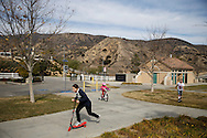 Shannon Waldman, 12, (in blue) and twin sister Katherine Waldman (in white) play with Cameron Waldman, 6, in Holleigh Bernson Memorial Park as methane gas leaks from the SoCalGas Aliso Canyon Storage Facility well SS-25 in the Porter Ranch neighborhood of Los Angeles, California on Sunday, January 3, 2016. The Aliso Canyon gas leak (also called Porter Ranch gas leak) was a massive natural gas leak that started on October 23, 2015. According to Wikipedia, an estimated 1,000,000 barrels per day was released from a well within the underground storage facility in the Santa Susana Mountains near Porter Ranch. The second-largest gas storage facility it belongs to the Southern California Gas Company (SoCalGas), a subsidiary of Sempra Energy. On Jan. 6, 2016, Governor Jerry Brown issued a State of Emergency. The Aliso gas leak carbon footprint is said to be larger than the Deepwater Horizon leak in the Gulf of Mexico. On Feb. 11, 2016 the gas company reported that it had the leak under control. On Feb. 18 state officials announced that the leak was permanently plugged. An estimated 97,100 tonnes of methane and 7,300 tonnes of ethane was released into the atmosphere, making it the worst natural gas leak in U.S. history in terms of its environmental impact. © 2016 Patrick T. Fallon