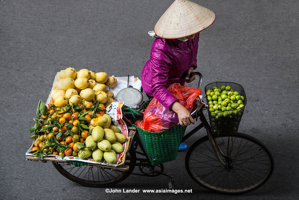 Hanoi Street Vendor Fruit  - Street Vendors, Hanoi Old Quarter - In Hanoi, life is convenient for shoppers, especially housewives. . No matter where you are, you can easily get anything you need from ubiquitous street vendors. They can make their living by carrying a yoke - baskets slung from each end of a bamboo pole, or from the back of a bicycle. Street vendors are everywhere  in Hanoi. They are up before sunrise, carrying and peddling everything from baguettes to brooms to baskets.