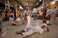 A man sleeps on the platform with his plastic jerry can filled up with the Ganges' holy water.