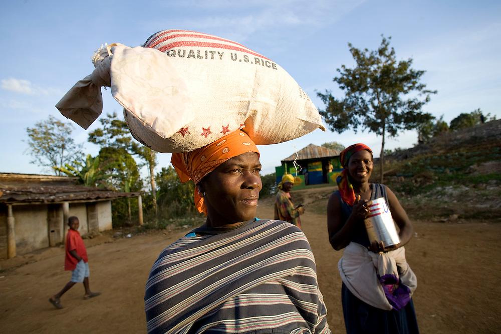 Women walk home after receiving food. Fonkoze distributes food relief to hurricane victims who are Fonkoze Solidarity Group members in Berdorange, (near Marigot), Haiti. Photo by Ben Depp 01.16.2009