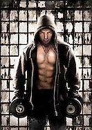 Muscular male in hoodie with top off in front of glass wall holding dumb bells.