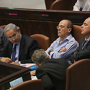 """Minister of Energy and Water Silvan Shalom (C) rests as he sits next to Israel's Prime Minister Benjamin Netanyahu (2L) Defense Minister Moshe (""""Boogie"""") Yaalon (L)  during a plenum session voting on the state budget, in the Knesset, Israel's Parliament, in Jerusalem, late night July 29, 2013. The Knesset approved the State Budget at second and third readings in the early hours of Tuesday morning in a 58-43 vote, following a 15-hour parliamentary session. Photo by Oren Nahshon"""