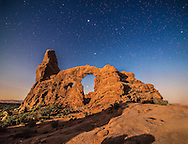 A moonlit scene at Turret Arch in Arches National Park, Utah, with Sirius shining through the Arch, Procyon above the Arch, and above it at top centre, Jupiter, near the Beehive star cluster. The stars of Gemini are right of Jupiter. The rising waning gibbous Moon provides the illumination.<br />