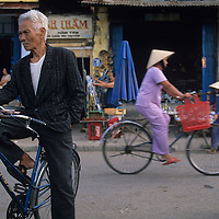 Asia, Vietnam, Hoi An, Man stands by bicycle on busy street along Thu Bon River near Central Market