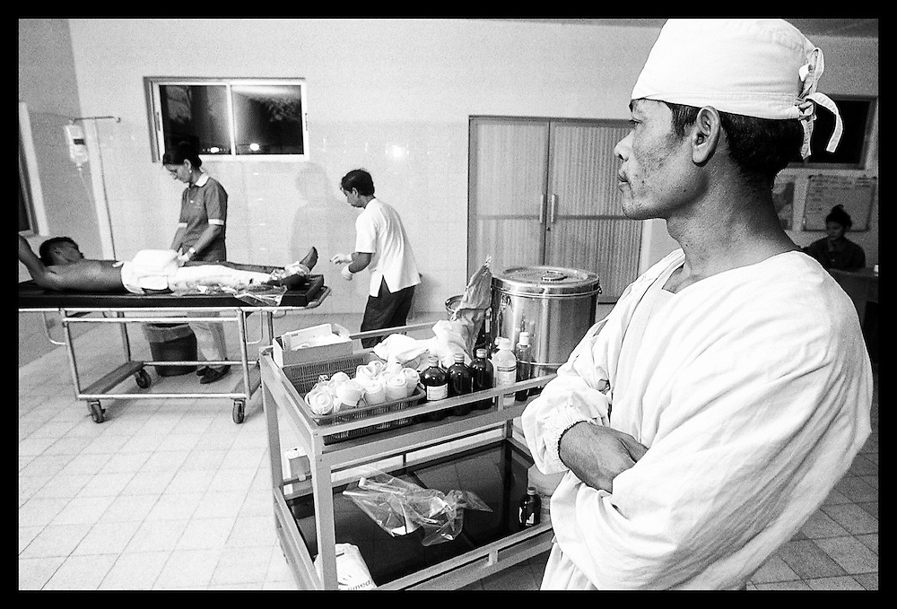 "Cambodian surgeons look on as Nil Sarak  is prepared for surgery Wednesday, March 17, 1999, at the modern trauma facility ""Emergency"" in Battambang, Cambodia.  Sarak was injured by a landmine while attempting to clear land he and his family recently settled in Bavil provience, 100 kilometers, west of Battambang."