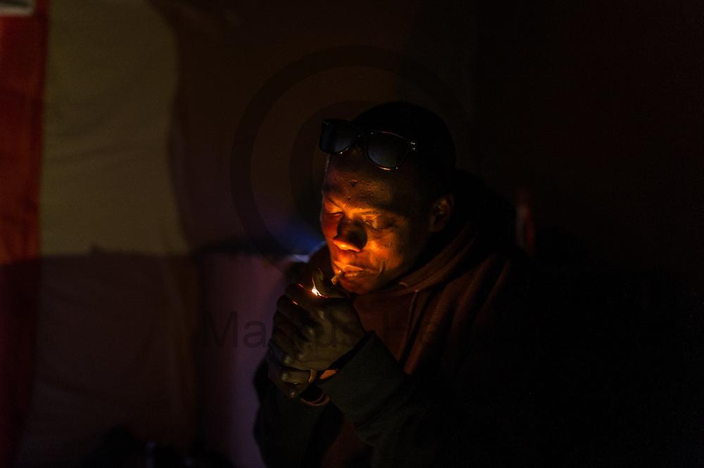 Calais, Frankreich - 16.10.2016<br /> Ein Migrant aus dem Sudan z&uuml;ndet sich im Dschungel von Calais in einer H&uuml;tte eine Zigarette an. Das Fluechtlingscamp an der Kueste zum Aermelkanal soll laut franz&ouml;sischer Regierung in den n&auml;chsten Tagen geraeumt werden. In dem Camp leben um die 1000 Fluechtlinge und warten auf die Moeglichkeit zur Weiterreise durch den Eurotunnel nach Gro&szlig;britannien. Photo: Foto: Markus Heine / heineimaging<br /> <br /> Calais, France - 2016/10/16<br /> A migrant from Sudan lights a cigarette to himself in the Calais Jungle in a hut. The refugee camp on the coast to the English Channel is to be cleared in the next few days, according to the French government. In the camp live around the 1000 refugees and wait for the possibility to travel further through the Eurotunnel to the UK. Photo: Foto: Markus Heine / heineimaging<br /> <br /> ------------------------------<br /> <br /> Ver&ouml;ffentlichung nur mit Fotografennennung, sowie gegen Honorar und Belegexemplar.<br /> <br /> Bankverbindung:<br /> IBAN: DE65660908000004437497<br /> BIC CODE: GENODE61BBB<br /> Badische Beamten Bank Karlsruhe<br /> <br /> USt-IdNr: DE291853306<br /> <br /> Please note:<br /> All rights reserved! Don't publish without copyright!<br /> <br /> Stand: 10.2016<br /> <br /> ------------------------------