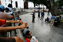 People listen to a preacher in Plaza Bolivar in downtown Caracas.