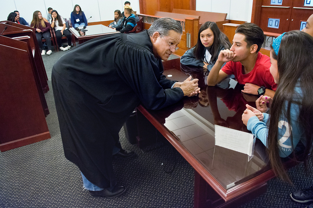 mkb042717a/metro/Marla Brose --Judge Frank Sedillo gives a group of 13-year-olds, including Diego Martinez, second from right, and Aurora Martinez, third from right, the scenario for a mock trial in his courtroom in the Bernalillo County Metropolitan Court, Thursday, April 27, 2017, in Albuquerque, N.M. About 70 kids, the children of court workers, argued mock court cases, toured the courts and learned about law enforcment procedures and evidence gathering during National Take Our Daughters and Sons to Work Day. Judge Sedillo's mock trial concerned a case about an NBA star's stolen basketball shoes. (Marla Brose/Albuquerque Journal)