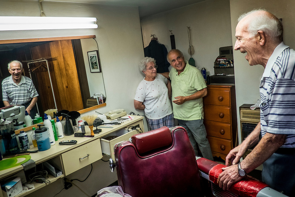 John Talarico looks on as his wife Margie talks with Monessen Mayor Lou Mavrakis in Tallarico&rsquo;s barber shop in the basement of his home in Monessen. Pa.<br /> <br /> Monessen, a third-class city, faces the same problems as th other former steel towns &mdash; declining population and tax revenue after the mills shut down. The city's population has dropped to 7,600 from a high of 20,268 in 1930.
