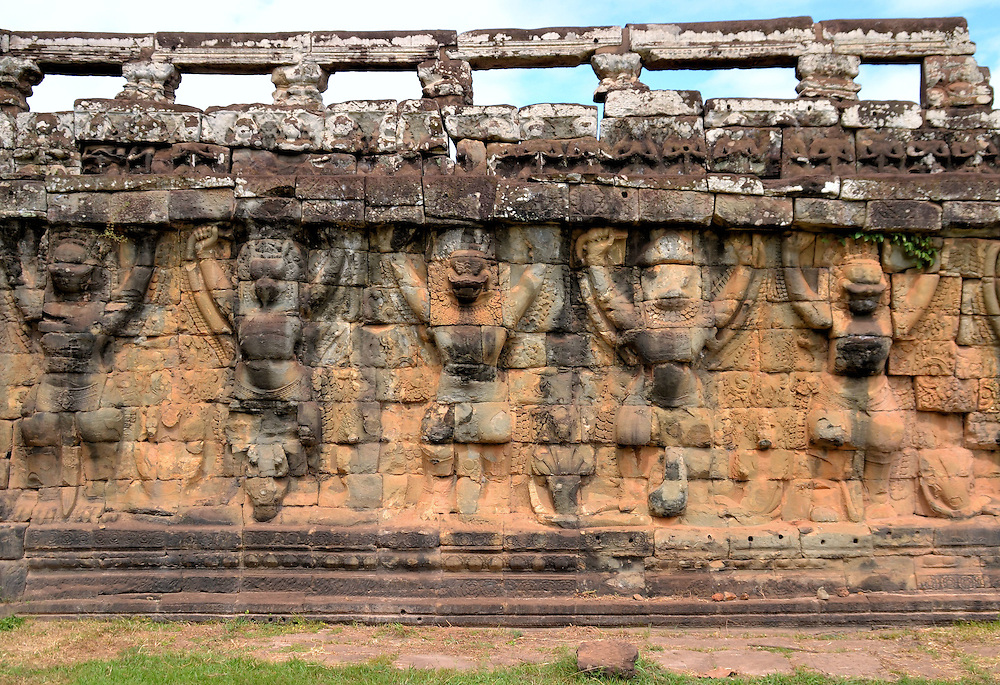 Terrace of the Leper King at Angkor Thom in Angkor Archaeological Park, Cambodia<br /> The Terrace of the Leper King is named after Yasovarman I. The king reigned from 889 &ndash; 910. He was called the Leper King because he suffered from leprosy before dying in 910. A section of this terrace is supported by a row of five garudas. This mythical creature with the head, wings and talons of an eagle and a human body is a powerful spirt in both Buddhism and Hinduism. Notice the faint reliefs of serpents at the feet of these great birds. The nāgas represent hatred and jealously. They are the enemy of the protective garudas.