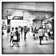 Commuters are completely unaware of police security camera watching over them as they congregate in front of the turnstiles of the commuter train stations that ferries local residents from the periphery to the center of Tokyo.  Japan.