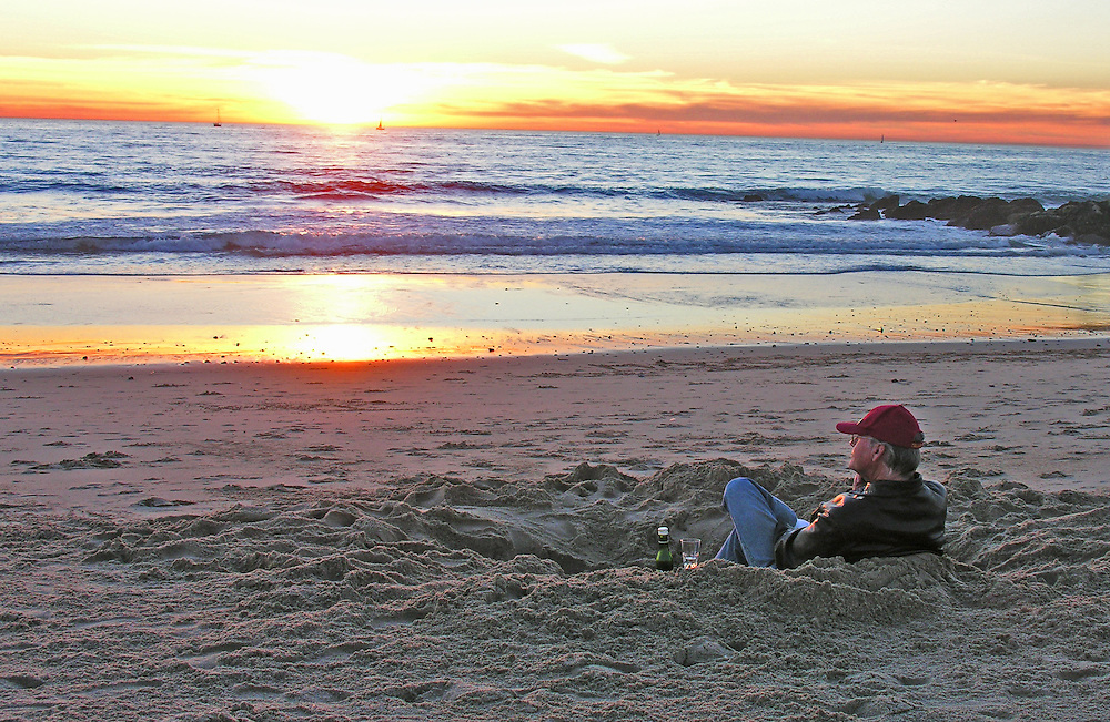 A man watching the sunset, enjoying a glass of wine on the beach.  El Segundo, California.
