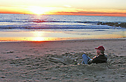 A man watching the sunset, enjoying a glass of wine on the beach.  El Segundo, California.