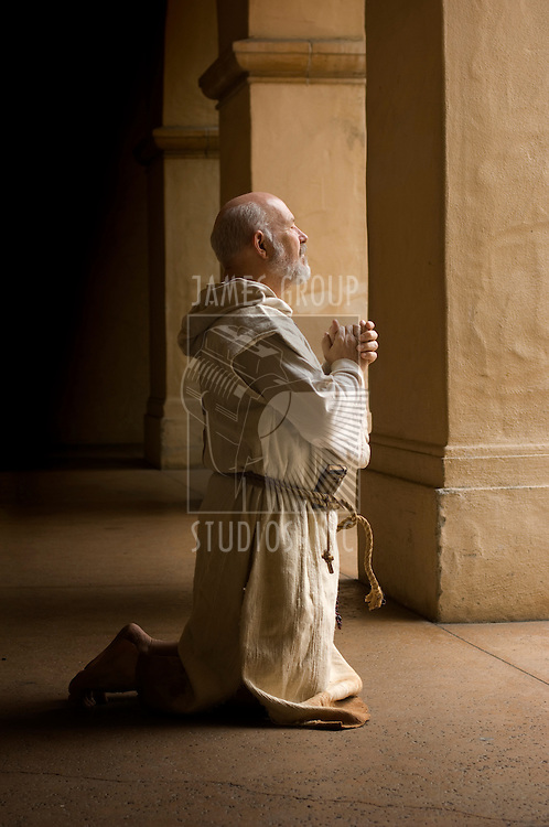 Barefood monk praying on his knees in a monestery