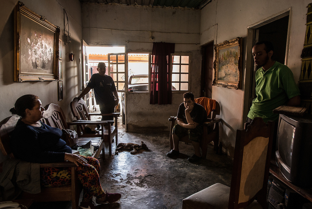 MARACAY, VENEZUELA - JULY 4, 2016: Mario Simeone and Evelin RodrÍguez hang out in their living room with their two schizophrenic sons, Gerardo and Accel.  The economic crisis that has left Venezuela with little hard currency has already hit its health system, leaving hospitals without antibiotics, surgeons without gloves and patients dying on emergency room tables.  But beyond the hospital wards, thousands more mental health patients—many of whom had been living relatively normal lives at home with their families under medication—are slipping back into relapse for lack of basic psychiatric medications which control their symptoms, medical experts say. PHOTO: Meridith Kohut for The New York Times