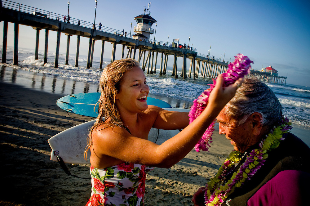 Interfaith blessing of the waves in Huntington Beach, California..Father Christian Mondor revecives a lei from a young girl that attended the service..Photographer: Chris Maluszynski /MOMENT