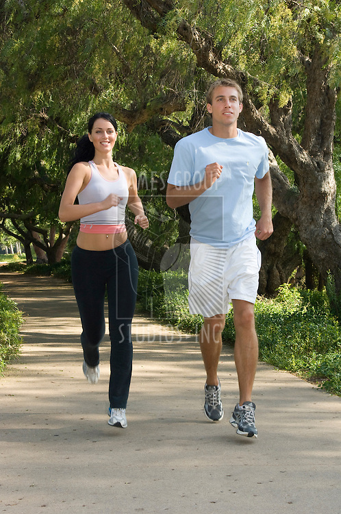 Young, attractive couple jogging in the city park