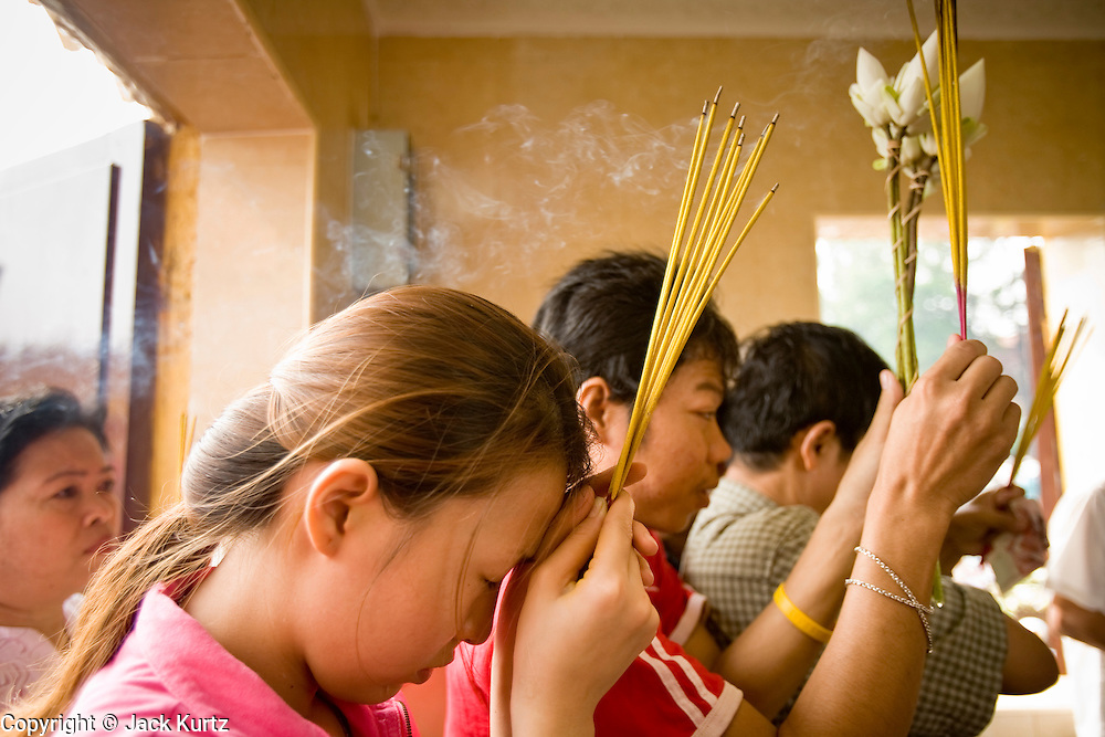 """14 MARCH 2006 - PHNOM PENH, CAMBODIA: People crowd into a small pagoda in front of the Royal Palace in Phnom Penh, Cambodia to pray. The pagoda serves as the """"spirit house"""" of the palace. The Cambodians (and Thais) build small spirit houses, which have great religious significance, in front of the homes and usually businesses. They pray at the spirit homes and frequently leave small offerings of fruit and small change in them. The spirit house for the Palace has become a public shrine and there are usually people there praying, leaving donations and lighting incense. Photo by Jack Kurtz / ZUMA Press"""